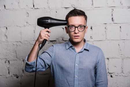 blow dryer: Male stylish hairdresser holding a blow dryer and shooting over grey brick wall