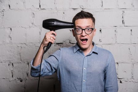 stupid body: Male stylish hairdresser holding a blow dryer and shooting over grey brick wall