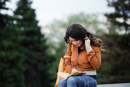 prettiness: Beautiful outdoors portrait of a woman with a book Stock Photo