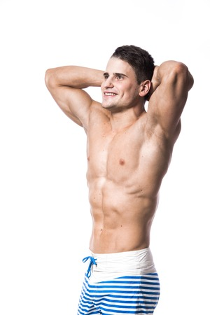 beach hunk: Young strong athlete on light background smiling Stock Photo