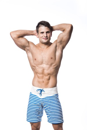 beach hunk: Young strong athlete on light background looking to the camera and smiling Stock Photo