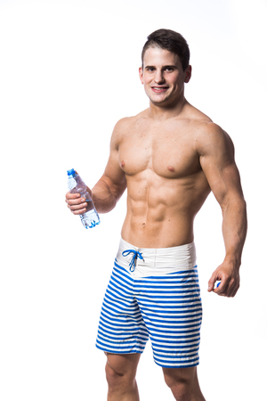 pectorals: Young strong athlete on light background looking to the camera and smiling Stock Photo