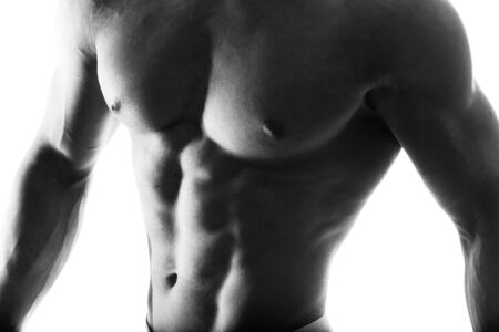 pectorals: Dark contrast shot of young muscular fitness man stomach and arm.
