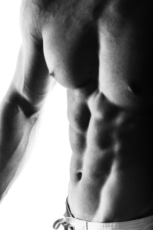 strong chin: Dark contrast shot of young muscular fitness man stomach and arm.