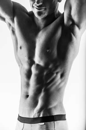 abdominal wall: Dark contrast shot of young muscular fitness man stomach and arm.