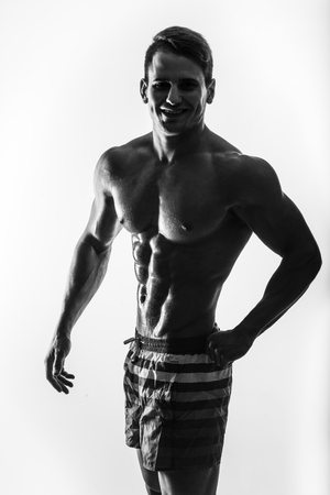 bad temper: Dark contrast shot of young muscular fitness man stomach and arm.