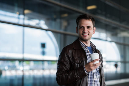 bristle: Stylish handsome young male traveller with bristle standing outdoors near the airport terminal. Man wearing jacket and shirt. Smiling person looking to camera holding cup of coffee.