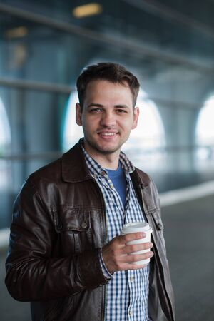 to go cup: Outdoor portrait of modern young man with coffee to go cup, smiling and looking to camera.