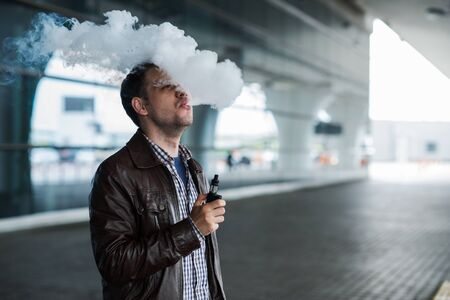 satisfying: Young man enjoying a satisfying e-cigarette standing in profile against airport terminal background.
