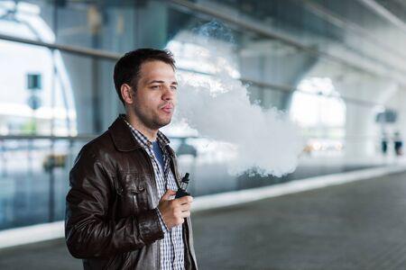 flight mode: Man with a bristle smoking e-cigarette vaporizer box mode outdoors near the airport terminal before flight.