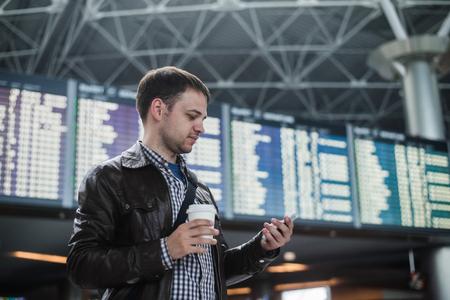 空港ターミナルでスケジュールのボードの前で携帯電話でコーヒーを飲みながら陽気な男。 写真素材