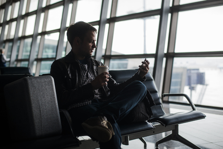homme en attente au salon de l'aéroport textos avec son téléphone intelligent.