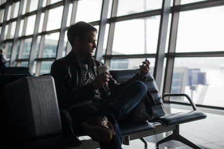 man te wachten op de luchthaven lounge texting met zijn smartphone.