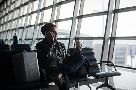 businessman waiting call: Portrait of young handsome man wearing casual style clothes sitting on the bench in modern airport using smartphone. Passenger travelling with luggage bag making call, while waiting for his flight. Stock Photo