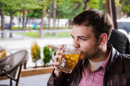 side bar: Man drinking beer. Side view of handsome young man drinking beer while sitting at the bar counter. Stock Photo