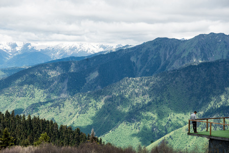 observes: Explorer observes an outstanding panorama in the mountains.