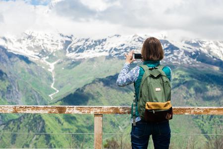 La muchacha de la mujer bastante joven permanece en la cima de la montaña y toma la imagen con el teléfono elegante sobre fondo hermoso. Foto colorida del viajero turístico femenino Foto de archivo - 57787996