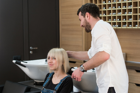 hairdressing saloon: Cheerful dark-haired man doing hairstyle for teen blonde girl in hairdressing saloon. Stock Photo