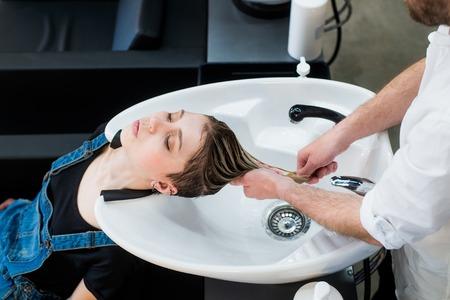 Hair care in modern spa salon. Male hairdresser washing teen girls hairs.