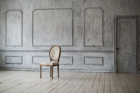 antique: Set of white wooden vintage chairs standing in front of a white wooden wall on light parquet floor.