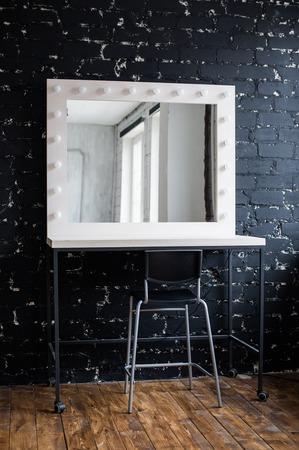 vistiendose: lugar de maquillaje de la mujer con espejo y focos en el estudio fotográfico de loft interior de la pared de ladrillo negro. Foto de archivo