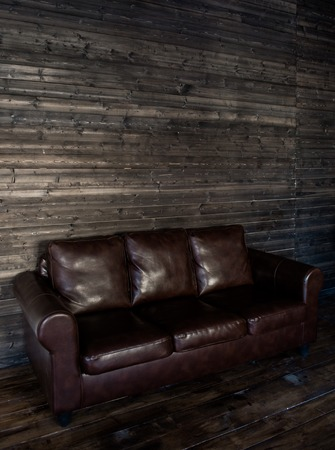 brown leather sofa: vintage brown leather sofa on a wooden wall and floor.