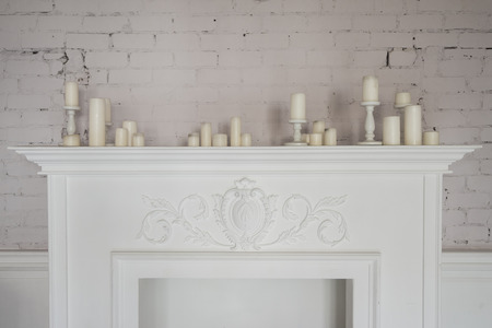 comfortable: Fireplace with beautiful decorations with candles in comfortable living room.