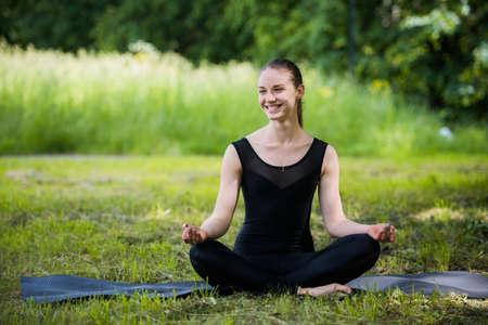 limber: yoga woman on green grass in lotus pose