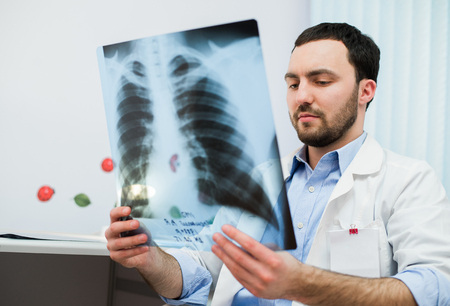 chest x ray: close up portrait of doctor looking at chest x ray in his office. Stock Photo