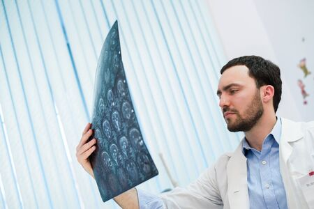 labcoat: Closeup portrait of intellectual man healthcare personnel with white labcoat, looking at brain x-ray radiographic image, ct scan, mri, clinic office background. Radiology department. Stock Photo