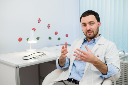 therapeutist: Friendly male medicine therapeutist doctor sitting in office, talking to patient and looking in camera. Medical help, physician reception or insurance concept. Physician waiting for patient.