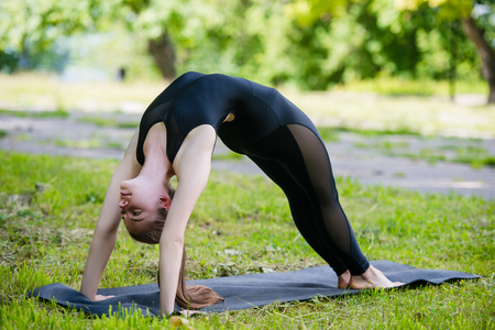 ushtrasana: Fit young beautiful woman wearing black sporty leggings working out outdoors in park on summer day, doing Bridge Pose, Urdhva Dhanurasana Upward Bow, Chakrasana Wheel posture.