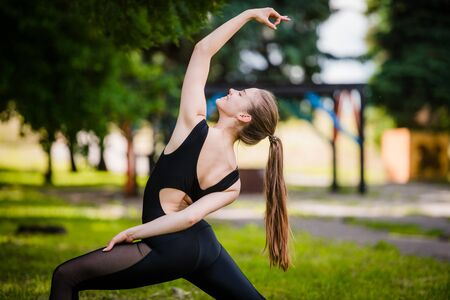 yogic: Pretty woman doing yoga exercises in the park.