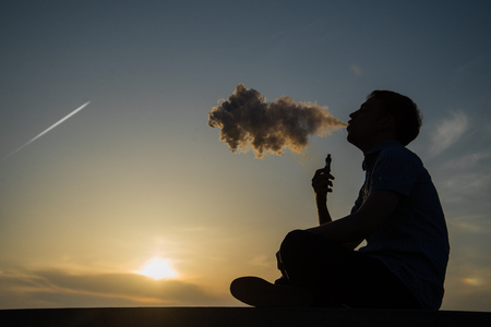 vaping young man with, produces vapor on sunset sky background at the sea coast promenade, place for text. Stockfoto