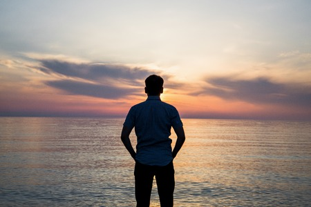 Young man standing at the beach in front of amazing sea view at sunset or sunrise and thinking about his future. Rear view. Standard-Bild