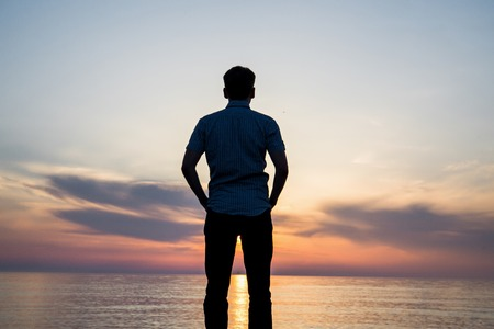 Silhouette of young man on the beach at sunset.