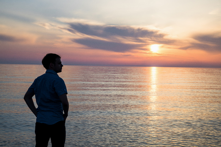 faraway: Young man standing at the beach in front of amazing sea view at sunset or sunrise and thinking about his future. Rear view. Stock Photo
