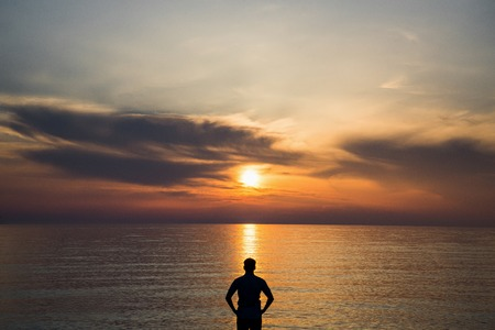 Young man standing at the beach in front of amazing sea view at sunset or sunrise and thinking about his future. Rear view. Stock Photo