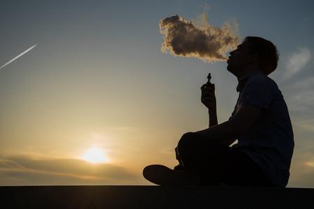 vaping、若い男は、テキストのための場所、海海岸遊歩道夕焼け背景に蒸気を生成します。