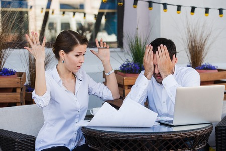 communicating: business people conflict working problem, angry boss argue scream to colleague businessmen and women serious argument negative emotion discussing report meeting at outdoors cafe during the lunch. Stock Photo