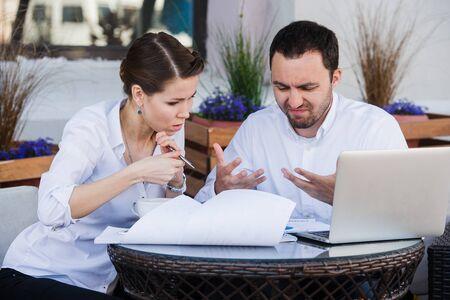 男性と女性のビジネス同僚の困難な問題に一緒に取り組んで。自分の顔に緊張した表情をいます。