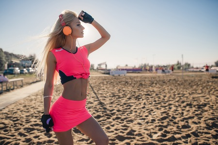 lithe: Fitness model athlete girl in colorful sportswear with headphones posing and listening music outdoors on beach or sports ground before workout at evening summer.