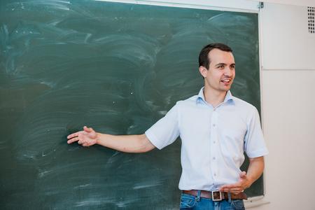 estudiantes adultos: Retrato de los estudiantes guapo joven o profesor en una clase en la que se�ala la pizarra en blanco y sonriente.
