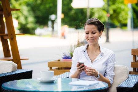 sidewalk talk: Portrait of a charming business woman chatting on her smart phone while waiting someone in cafe outdoors, gorgeous female using mobile phone while sitting in cozy restaurant in the fresh air during lunch.