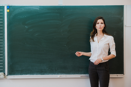 Woman pointing finger at blank board. School teacher pointing the finger at a blank board. Student stands at the blackboard. Business woman presenting the idea to the board. Girl in the school Фото со стока