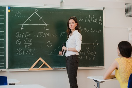 pupils: Female Teacher Answering Pupils Question In Classroom