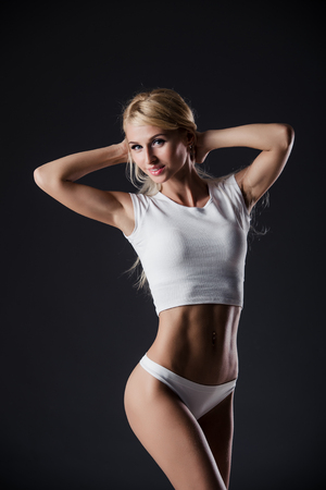 motivator: Fitness blonde woman shows her body. Fitness motivation. Perfect female sports figure. Fitness woman posing in the studio. Fitness photo shoot in the studio. Fitness bikini.
