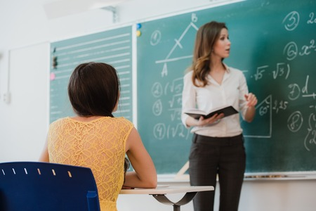 mates: Teacher or docent or educator giving while lesson in front of a blackboard or board a sheet of paper and educate or teaching students or pupils or mates in a school or class.
