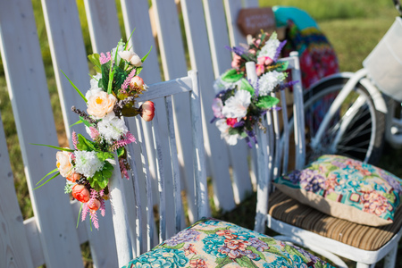 gorinchem: Beautiful open terrace in the garden with tiffany coloured vintage white chairs, colorful velvet pillow and fence palisade, bicycle on background decorated flowers in boho style Stock Photo