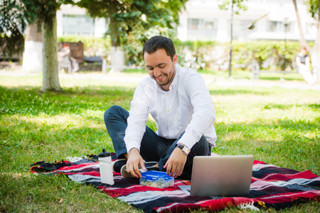 sandwitch: Businessman working in the garden and eating lunch. Stock Photo